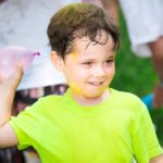 A young participant enjoying the water balloon toss at the 2016 Muddy Puddles Mess Fest.